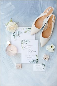 Wedding Details Flatlay against Dusty Blue background with fresh Florals, nude heels, chanel perfume, and Mrs. Box ring Box Wedding Vendors, Wedding Tips, Wedding Details, Lakeside Wedding, Vineyard Wedding, Round Table Centerpieces, Arch Flowers, Greenery Garland, Chanel Perfume