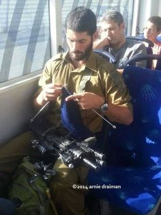 IDF soldier knitting - continental style. Sticks and a gun!
