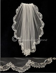 The scalloped edge of this waist length bridal veil is embroidered with a silver swirl and floral design. Beads and rhinestones give the design some shine. It is 30 inches long and 72 inches wide, on