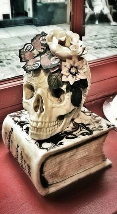 I'm thinking I could TOTALLY make this for her birthday with a plastic skull, puffy paint for the raised design, butterflies and flower accents from the dollar store. Bone colored spray paint...a book from the thrift store, I'm thinking a white tightly woven burlap to cover the book and fabric paint for the design on the cover. She'll love it!