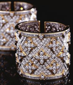 PAIR OF DIAMOND CUFF BANGLES, REPOSSI.  Each hinged cuff designed as a wide band of pavé-set brilliant-cut diamonds highlighted by quatrefoil motifs similarly-set, the borders composed of rows of step-cut diamonds, mounted in white and yellow gold,    signed Repossi, Italian assay marks, accompanied by pochettes.   internal circumference approximately 160mm,