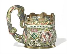 A Silver-Gilt and Cloisonné Enamel Tea Glass Holder  Marked K. Fabergé with the Imperial warrant, Moscow, 1896-1908  Cylindrical, the convex lower section enameled with varicolor shaded stylized flowerheads amidst foliate scrolls and geometric motifs on green, black and oxidized grounds, the shaped openwork rim with a repeating band of flames and stylized scrolls