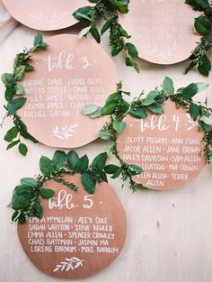Unique rose gold circular table cards topped with greenery