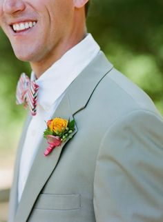 Blossoms in shades of peach and watermelon add a fun pop of color to the groomsmen's boutonnieres. Wedding Photographer: Todd Rafalovich Photography.