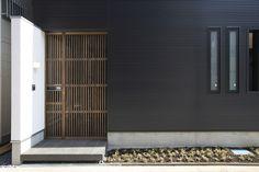玄関の風景。門扉としての格子戸の先に玄関ドアがある。ガルバリウム鋼板スパンドレルの黒い外観に、左官壁と木製の格子戸が柔らかい印象を加える。
