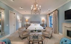 A sparkling chandelier, tufted silk furniture and a blue-and-cream color palette set an elegant tone in Tori Spelling's master bedroom in Encino, Calif. Other features of the stylish suite include a fireplace, a large balcony, a spa-style bathroom and a custom-built, walk-in closet.