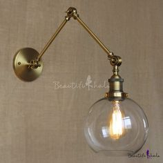 Adjustable Indoor Wall Lamp with Clear Glass Shade in Brass Finish