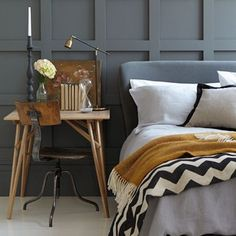 This bedroom would be stunning solely with the striking dark grey wall panel and monochrome bedding, but the addition of the rich ochre throw, writing desk, vintage chair and chic accessories adds an extra element that takes this stylish scheme to a whole new level.   Paint by Little Greene (Scree)
