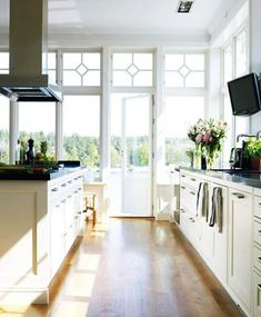White kitchen with dark counter tops. Love the windows flooding in lots of natural light, and providing a great view.
