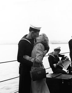 A sailor kisses his girlfriend as the HMS Black Swan returns to England.