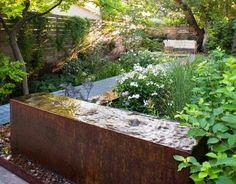 Table d'eau en corten dans un jardin