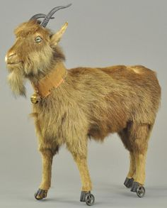 """*LARGE GOAT ON WHEELS ~ Germany, large mohair goat, glass eyes, leather ears, metal horns + cloth collar w/brass bell. 14""""."""