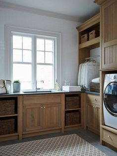 Laundry room with hanging rod, wash sink, and storage.