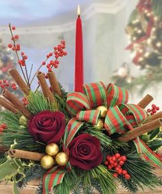 Centerpiece with cinnamon stick and red roses. by Marco Island Florist