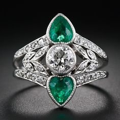 A bright-white and sparkling antique cushion-cut diamond, weighing two-thirds of a carat, is accompanied north and south by a gleaming pair of bright green heart shaped emeralds in this elegant and highly distinctive Edwardian jewel, finely handcrafted in platinum - circa 1915. The split 'V' shaped ring shank glitters with tiny European-cut and single-cut diamonds, embracing a diamond-set leaf motif twinkling on each side of the central diamond