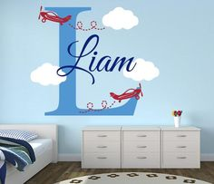 In this name wall decal a large capital letter covers the spotlight of the wall from which two planes are flying away in the sky where there are some clouds.