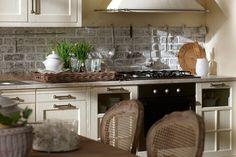 Cucina con piccola parete di mattoni a vista
