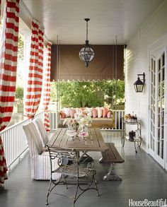 On the other half of the long porch, big, beautiful striped curtains in Oasis Awning from Thibaut's Portico  - HouseBeautiful.com