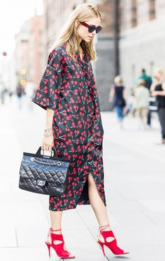 Pernille Teisbaek wears a cherry print midi dress with Aquazzura red heels, a Chanel bag, and Céline sunglasses
