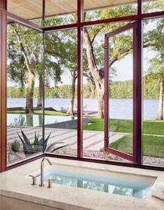 In this modern master bathroom, a deep soaking tub has plenty of windows that provide natural light and views of the lake. #Bathroom #SoakingTub #Windows #ModernBathroom