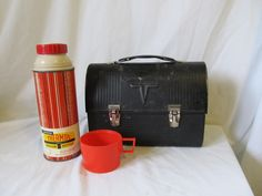 Vintage 1960's black metal lunch box with original thermos included. I remember my dad had this lunch box and thermos! My mom would send my dad out the door for a hard days work after filling his thermos with coffee and his lunch box with probably a peanut butter sandwich (his fave) and other goodies to sustain him for the day. Ohhh the memories   : )