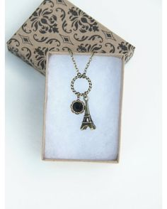 Paris is always a good idea! This Eiffel Tower Charm Necklace is a fun piece to wear with any outfit! The black crystal gives this necklace a striking elegant look. The Eiffel Tower and black crystal dangle from a decorative rope-like center piece.