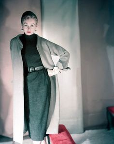 Model is wearing a pale grey tweed long coat with french cuffs, charcoal grey Heller worsted jersey turtleneck dress with belt and charcoal grey knit hat, all by B. H. Wragge. Also wearing chamois colored gloves by Alexette Bacmo and gilt half melon earrings by Elsa Schiaparelli, 1953.