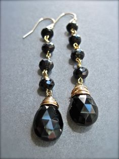 Black spinel gemstone gold dangle earrings. AAA quality black spinel briolettes are wire wrapped and hang from a series of black spinel rondelles. The earrings measure just over 2.5 inches (6.5cm) and are finished with 14K gold filled ear wires. These earrings are very elegant- a