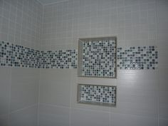 Contemporary tiled shower with recessed soap and shampoo shelf. Tiles above and below the glass mosaics are the same line but different sizes.