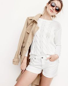 J.Crew women's washed cotton trench coat, cotton cable sweater, denim short in white and Betty sunglasses.