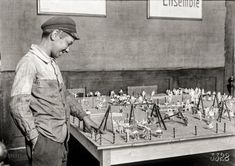 """July 1918. """"Alex, a 14-year-old working boy in St. Etienne, France, was found intently studying the playground model at the Children's Welfare Exhibit of the American Red Cross. He has been working since 11 years of age, and said: 'On account of the high cost of living, I now get four and a half francs a day'."""" 5x7 inch glass negative by Lewis Wickes Hine for the American Red Cross."""