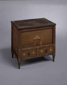 Eastern Tennessee, 1820-1830, walnut, poplar, HOA: 16 3/4; WOA: 16 7/8; DOA: 11 1/4 MESDA # 2500. This small chest is difficult to attribute to any given county or town. Its inlay is related to other Tennessee furniture, but its joined construction suggests a rural mountain origin. The use of nailed leather straps for hinges reinforces this supposition. The primitive nature of the inlay, particularly the elevation of a brick house, resembles that of embroidered samplers of the period.