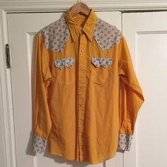 Vintage Men's Western Orange Button Down Shirt Vintage men's vintage bright yellowy-orange Western-style button down shirt. Muted floral print on shoulders and top rear, at pockets and at sleeve cuffs. Classic Western shirt styling; collar with collar stays inside for shaping, triangles at shoulders, dual chest pockets with double pearl snaps, pearl snap placket with single button at top, long sleeves with pearl snap cuffs, and curved hemline. Lightweight. Size 16-34. Good vintage condition…