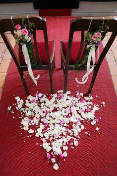 Hochzeitsstühle dekoriert mit Rosen in Rosa. Auf dem roten Teppich wurden die Rosenblätter verteilt. © bilderstoeckchen - Fotolia #hochzeitsdeko #kirchendeko #rosen