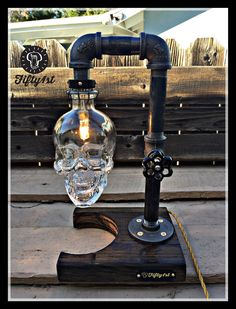 From Fifty1st comes another quality piece Max. This table lamp features a reclaimed wood base, steal pipe construction, a small yet powerful halogen bulb, stunning reclaimed Skull Vodka bottle and and a fully functional dimmer water valve switch! Features: • Reclaimed solid wood base •