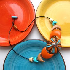 Jewelry Photography.  Beautiful use of plates as props.  Necklace pops against the colors.