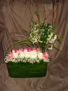 Roses, bear grass and wax flowers with some curly willow and myrtle.