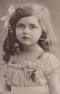 She is wearing Lily of the Valley in her hair and on her blouse. <3 my oldest and youngest's birth flower