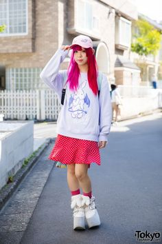"Today, Sebone is wearing a Listen Flavor ""Nasty"" bunny sweater, a resale polka dot skirt, pink socks, and white platform shoes with bunny ears from Yosuke. Her accessories – from 6%DOKIDOKI and Kuchidake Bancho – include a pink dragon cap, ear studs and hoop earrings, a coffin ring, a pentagram ring, and a cross ring."