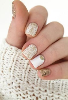 Tribal inspired white and gold nail art design. As you can see the nails are designed in various patterns and shapes in gold glitter to pop out from the white base.