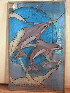 My neighbor made this delightful stained glass piece which I acquired to give to my son who is very fond of dolphins.