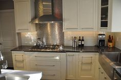 cuisine aménagee moderne facade meubles coloris ivoire credence en carrelage inox hotte aspirante en inox