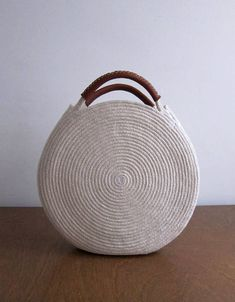 Round white bag made out of cotton rope and up-cycled soft brown leather. This bag is durable and roomy enough to fit all your necessities - measures about 12 inches across and 2 inches deep, with about 3 inch handles. Find a simple cotton rope basket bag without leather handles here: