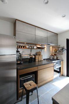 -キッチンカウンター- Ⅱ型のオーダーメイドキッチン。オーク突き板の面材をベースにアンティーク感のある真鍮ハンドルや、網入りの型ガラス、ステンレスの扉などを組み合わせました。壁面の吊り戸棚はフラップ扉、ダイニング側には、オープン棚や、引き出し式のデスクを造作したり、、と随所にこだわりを詰め込んだキッチンが出来上がりました。 ※キッチンカウンターの設置には、別途設備工事が必要です。