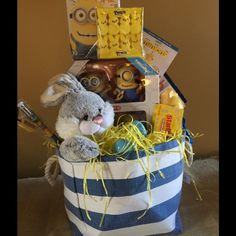 MINIONS THEMED EASTER BASKET Take the stress out of the holidays with a gorgeous gift basket with item carefully selected by me for this Minion Themed Basket  Includes pack of 4 large Posesble minions , stuffed bunny, box of 10 Minion fruit snacks. Box of Starburst, Box of Minion gunmies, Minions Blu Ray DVD Movie, Jumbo Minions Pencil and sharpener, pad of letter practice Minion paper. Minions water bottle. Comes in reusable canvas storage bin, plastic eggs, Peeps and grass. Ready for  gift…