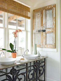 Charming Storage - Salvaged pieces add vintage charm to this bathroom. Next to this vanity, old shutters replace an ordinary door on the medicine cabinet. The shutters are held together in the center by the original hardware, but the door opens from the side to reveal built-in shelves and a mirror.
