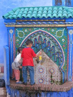 Chefchouen, Morocco -- Fetching water from a colorful fountain.