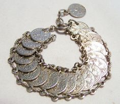 Vintage faux coin linked bracelet Silver tone stamped coins each connected by oval links Unsigned Adjustable length 7.5-8.5 inches Good vintage condition  International buyers welcome, I can ship 3 jewelry items for 13.00 USD, over charges are automatically refunded prior to shipping Flat rate Priority shipping is optional 83116  International buyers welcome  Want to see more great bracelets? Click here: https://www.etsy.com/your/shops/GretelsTreasures/sections&#...