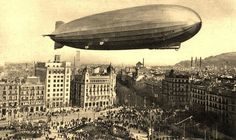 The Graf Zeppelin over Plaça de Catalunya, Barcelona 1929. Probably a fake of that time, zeppelins were in fashion and postcard makers added zeppelins to the sky. In this case the dirigible is too low to be safe over a built area.