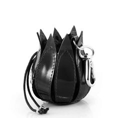 ??A sleek addition to the ever popular by-lin range, this tulip purse can be clipped onto the inside of your bag, ensuring you never lose those pesky coins again. It's drawstring clasp allows it to open much like a flower, and it's classic black colour makes for a great evening accessory or a subtle companion for your daytime bag. Dimensions: 7cm x 6cm